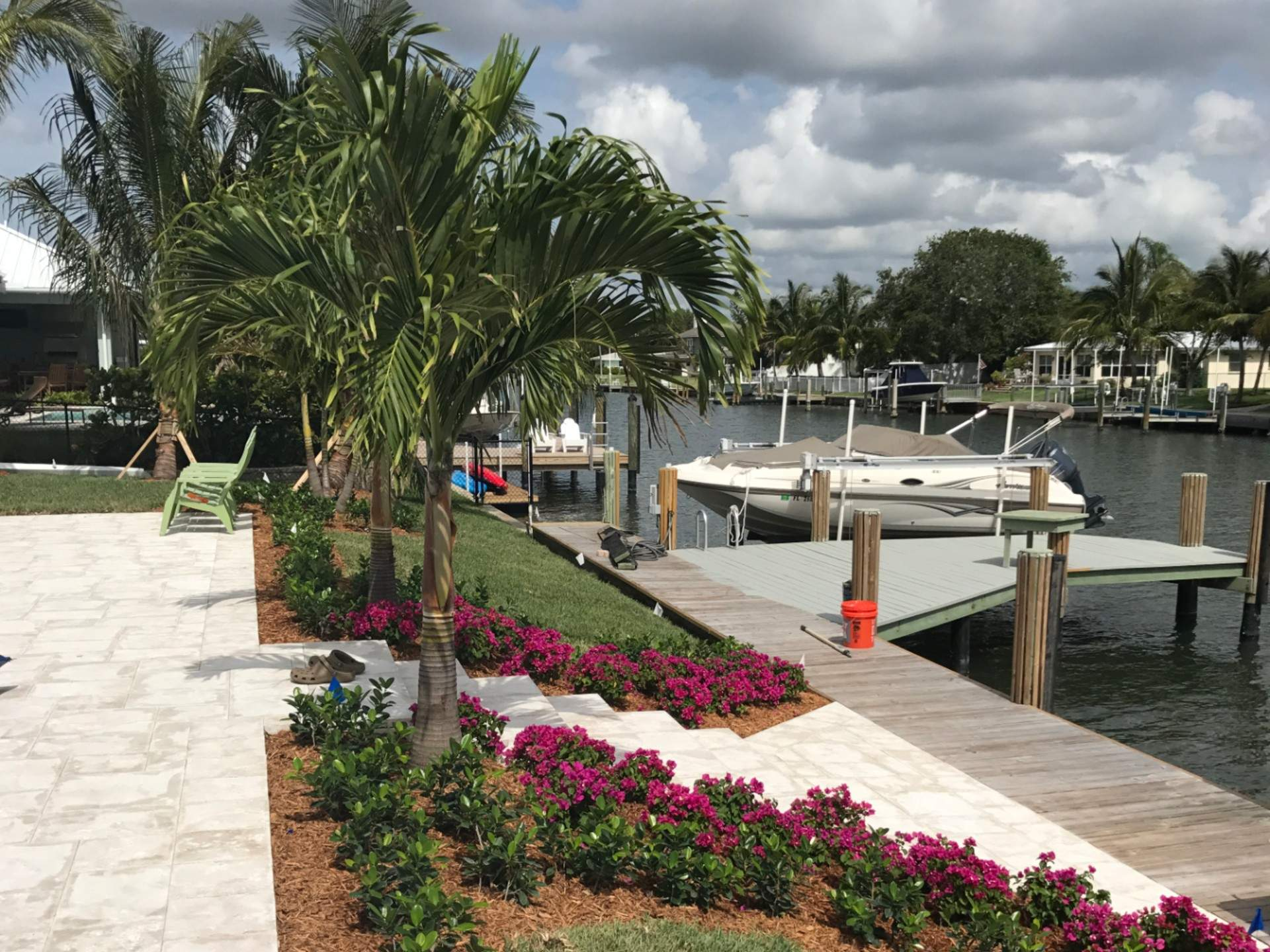 Palm trees and flowers in front of a dock with a boat